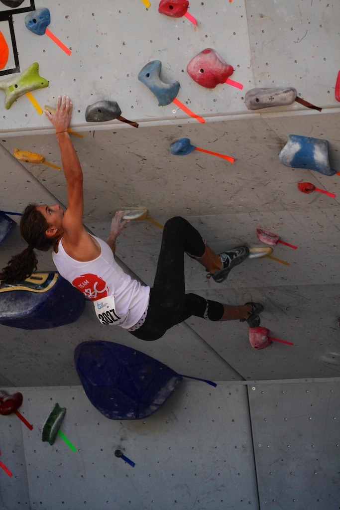 Pulling herself up over the ledge, a climber competes in Sunday's boulder challenge