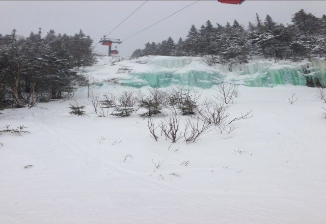 green waterfall under gondo being covered by falling snow - wonderful st patties day. New snow coming tuesday enjoy the end of season midweek.