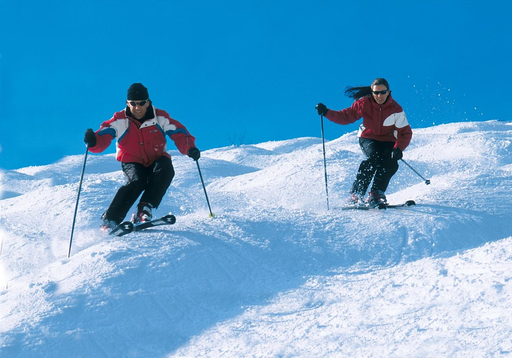 Two skiers make their way down the slopes of Crystal Mountain, Michigan