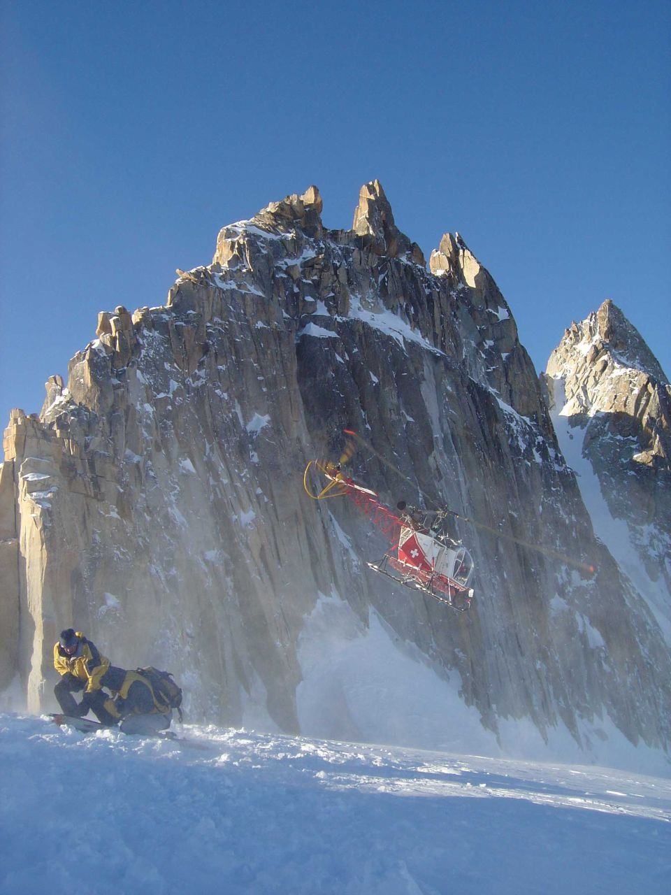 Helicopter hovering above snowy mountain
