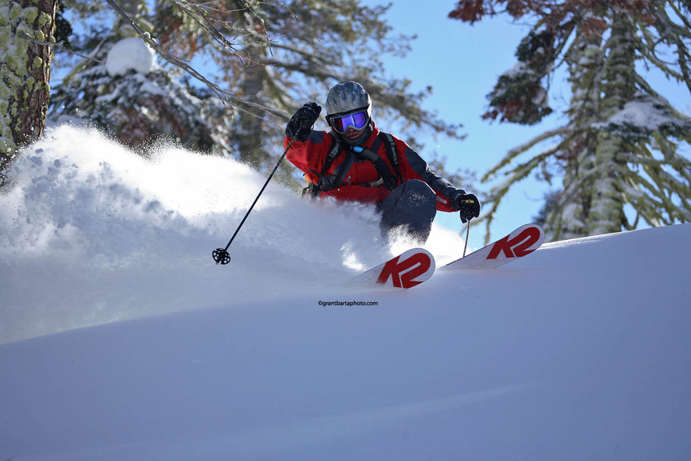 A skier avoids a tree and enjoys new powder at Sugar Bowl Ski Resort, California