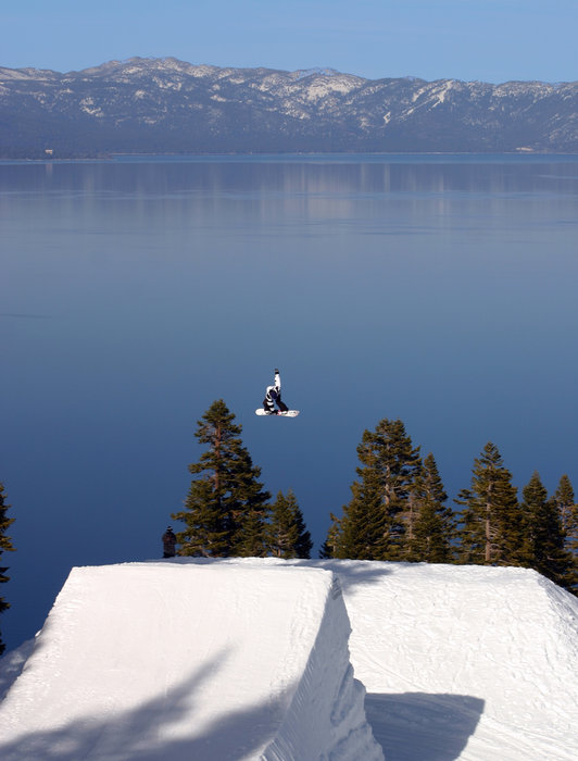 A snowboarder gets a great view of Lake Tahoe off a jump at Homewood in California