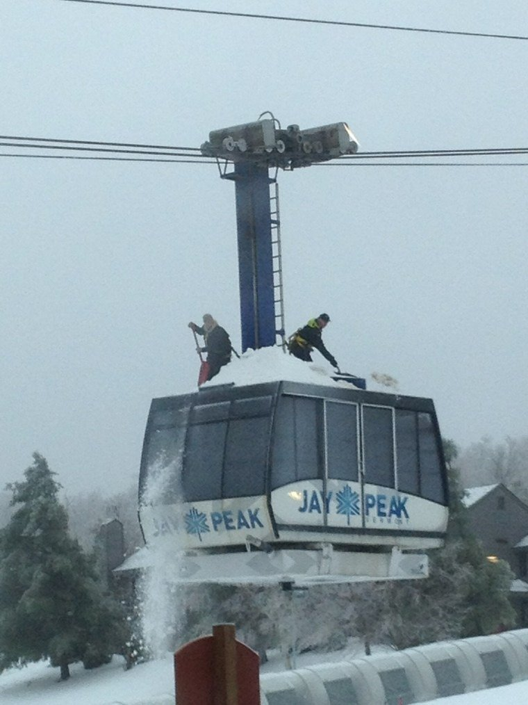 Workers shoveling cable ice from the roof of the tram at Jay. The mountain is closed today because of the ice storm.