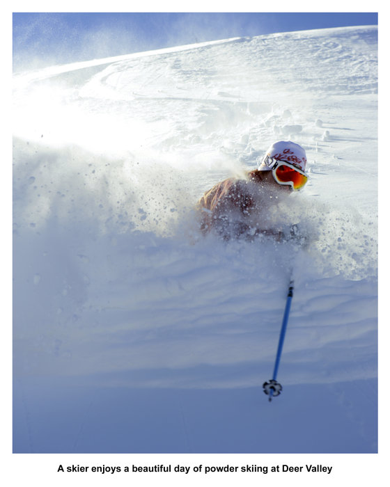 A skier enjoys a beautiful day of powder skiing at Deer Valley.