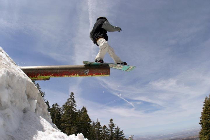 A boarder jibbing off a pipe at Mt. High, CA.
