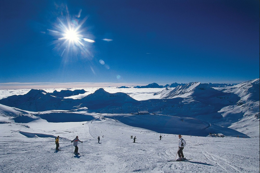 Skiers on gently sloping wide piste