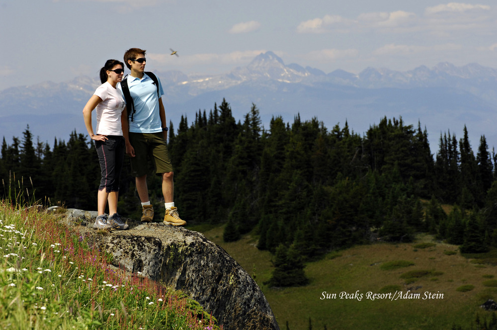 Hiking couple standing on rock in Sun Peaks