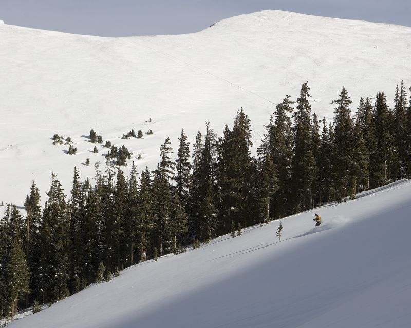 A skier gets powder in Keystone, Colorado's Independance Bowl area with a media crew.