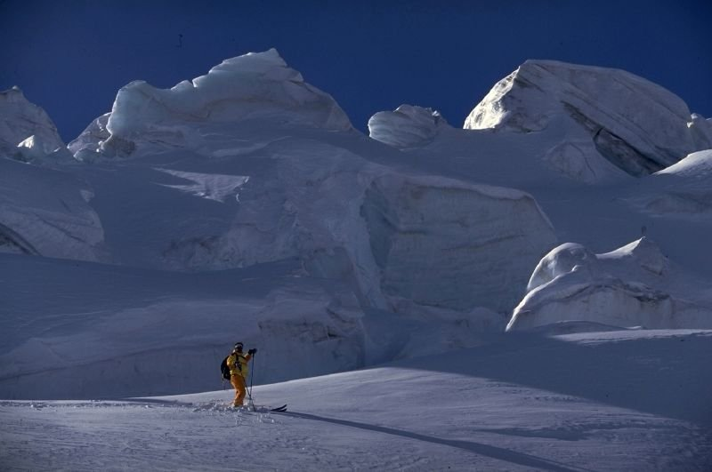 A skier pauses near the craggy ice over Saas Fee.
