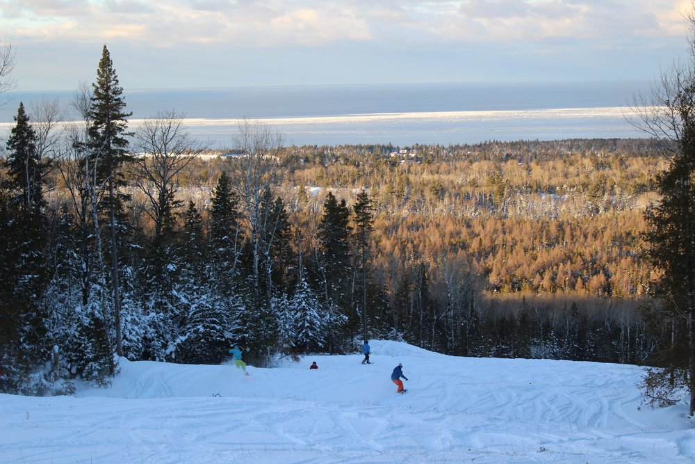 Snowboarders descend Voodoo Mountain with the sun on Lake Superior. - ©Louise Kremer/Voodoo Mountain
