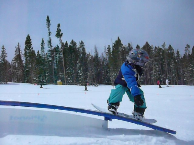 Kid snowboarder, Wesley Muresan on rail in snowpark at Sundown Mountain, Iowa.
