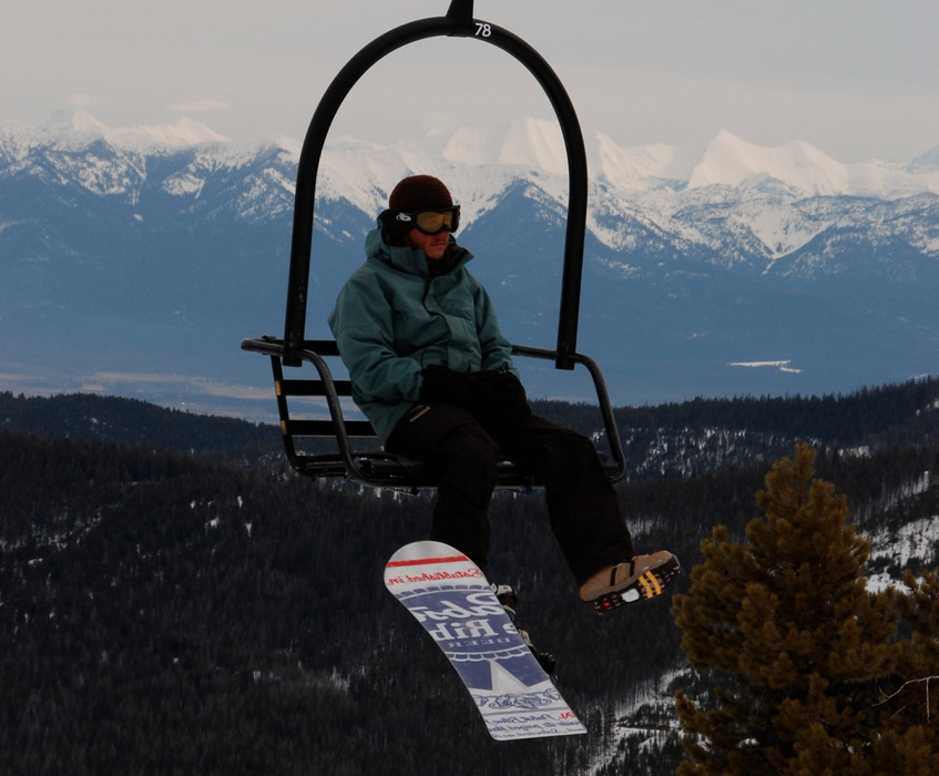 A snowboarder rides a lift at Blacktail Mountain. Photo by Becky Lomax. - ©Becky Lomax