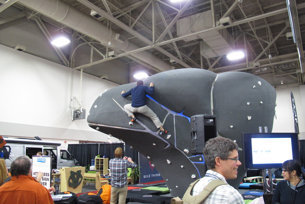 Eight hours of artificial light on the trade show floor can make anyone a bit antsy. Luckily, you can exert that pent up energy on the in-house climbing wall at Winter OR. - ©Dan Kasper