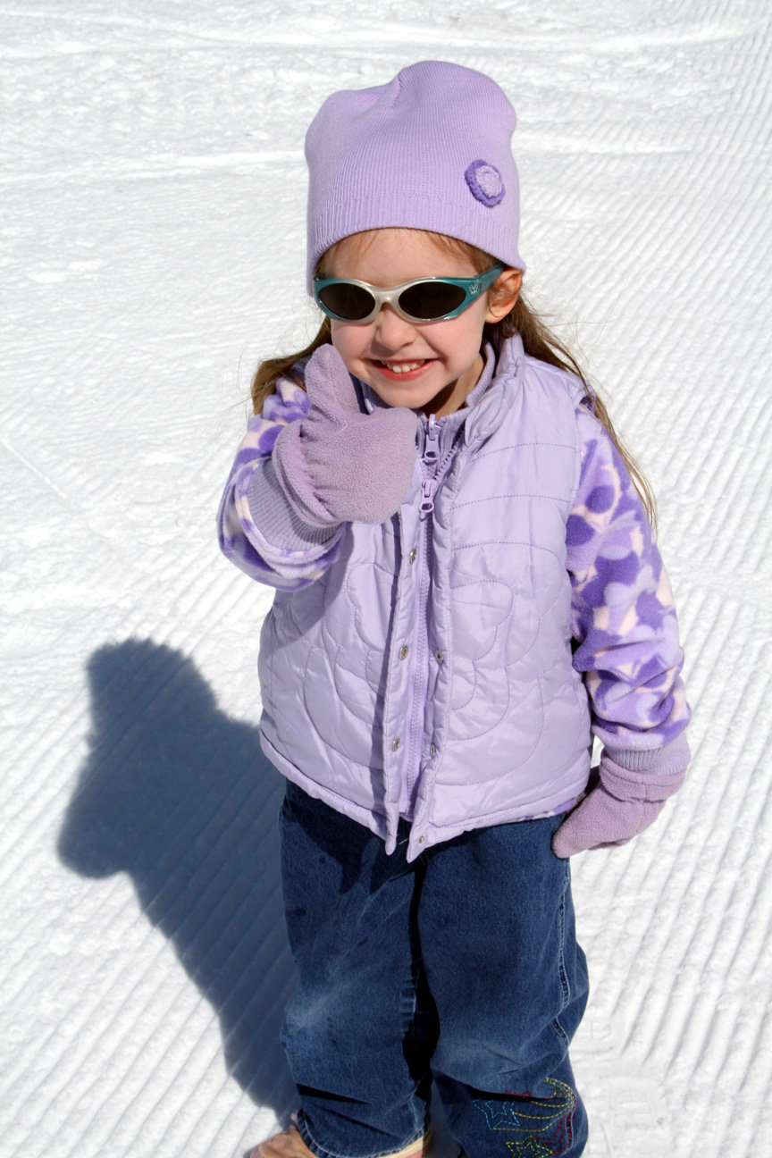 A young girl gives a thumbs up on a groomed run in Indianhead Mountain, Michigan