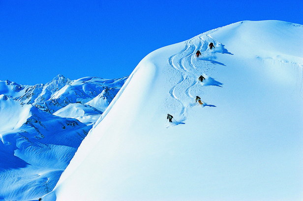 Skiers slaloming over powder at St Anton, AUT. - ©St. Anton Tourism