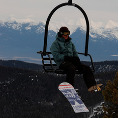 A snowboarder rides a lift at Blacktail Mountain. Photo by Becky Lomax.