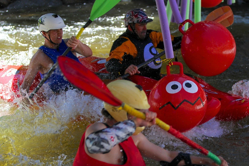 Kayakers charge under the bridge and into the main hole during the 8 ball challenge. - ©Tim Shisler