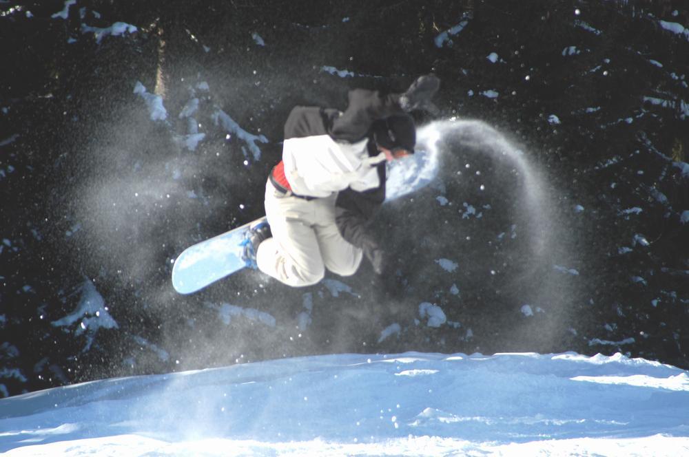 A snowboarder kicks up powder at Söll, AUT.