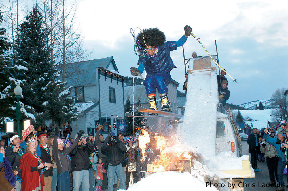 This skier jumps over fire during a Mardi Gras parade in Crested Butte, Colorado