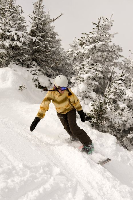 A snowboarder in deep snow at Smugglers' Notch, Vermont.