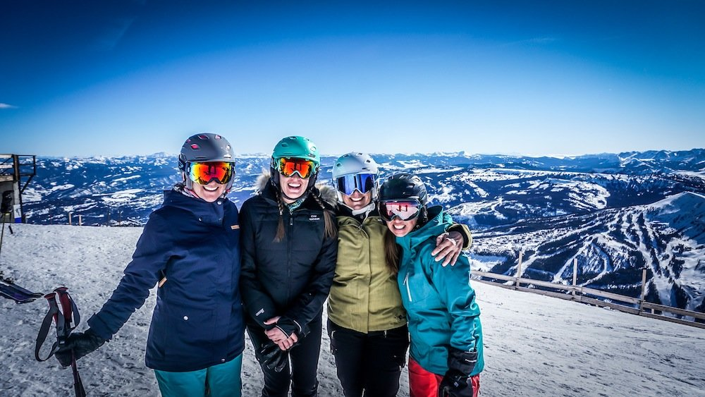 Happy skiers stand at 11,166 feet on top of Big Sky's Lone Peak. - © Eric Slayman