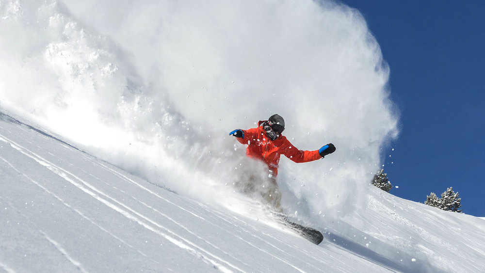 A snowboarder drops a mean rooster tail at Snowbird. - © Matt Crawley