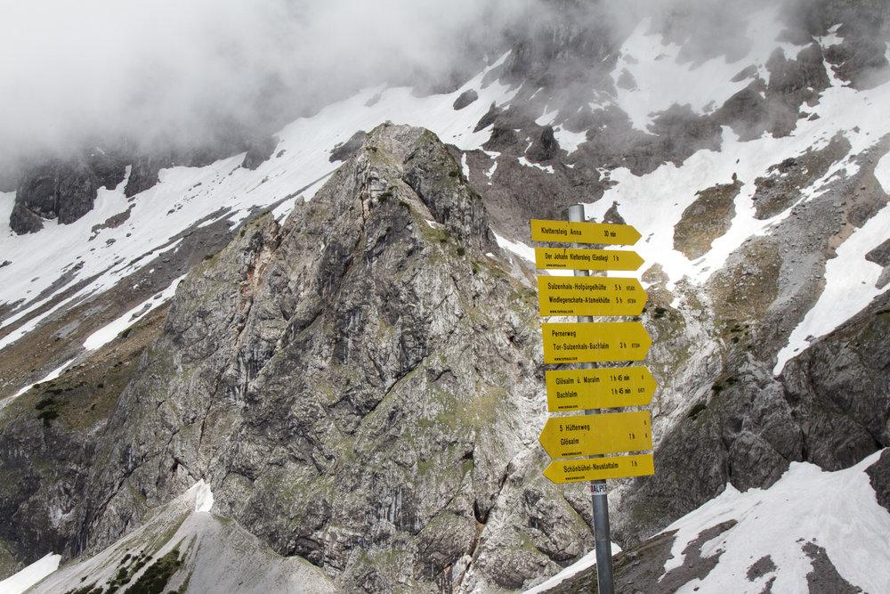 Wegweiser an der Südwandhütte. Im Hintergrund die Wand, durch die der Anna-Klettersteig verläuft. - ©Bergleben.de