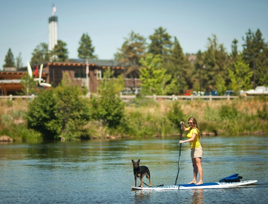 A paddleboarder cruises through Bend's Old Mill District. - © Craig Zagaurski