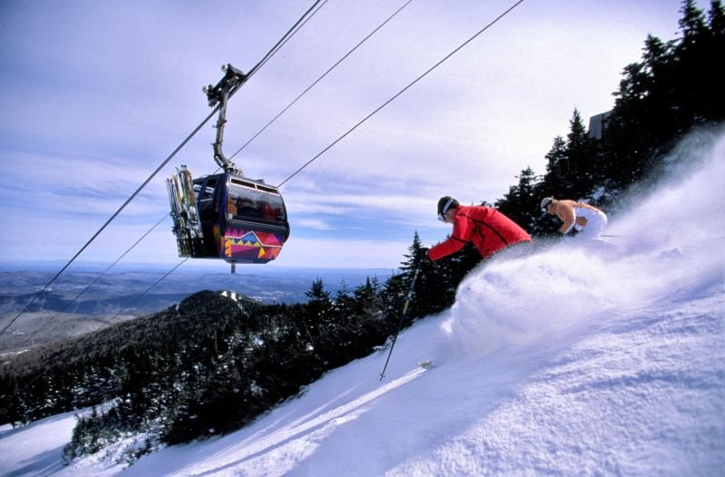 Freeskiers coming down while a gondola goes up at Killington VT