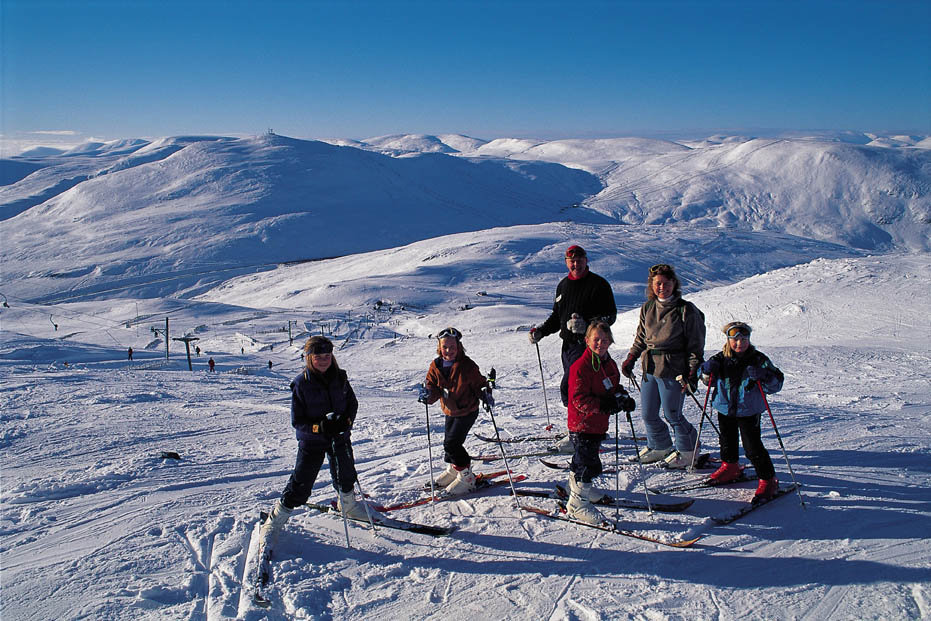 A family group poses for a photograph at the top of one of the runs on Meall Odhar (A Munro at 3019') at the Glenshee Ski Centre, northeast of the Spittal of Glenshee, Aberdeenshire.
