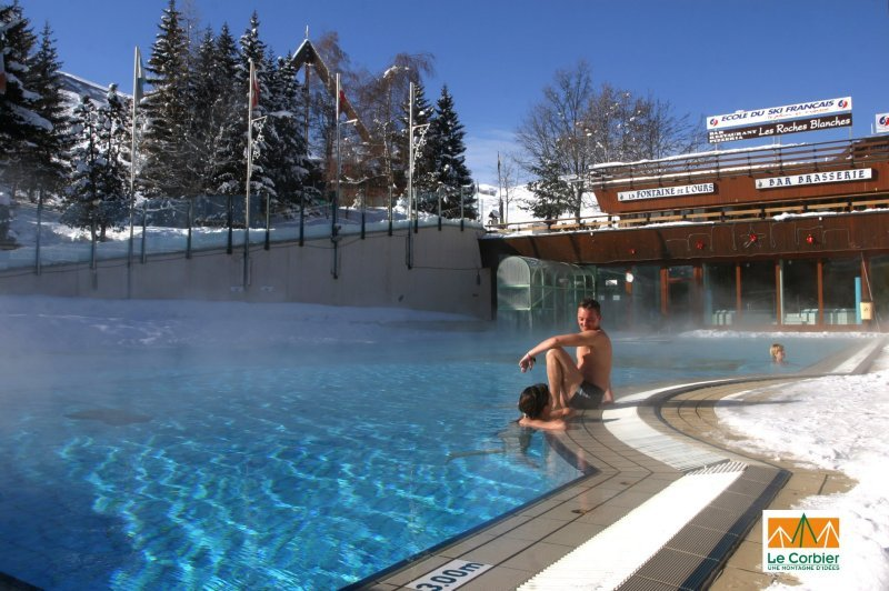 Visitor sitting on the edge of the pool at Le Corbier, France.