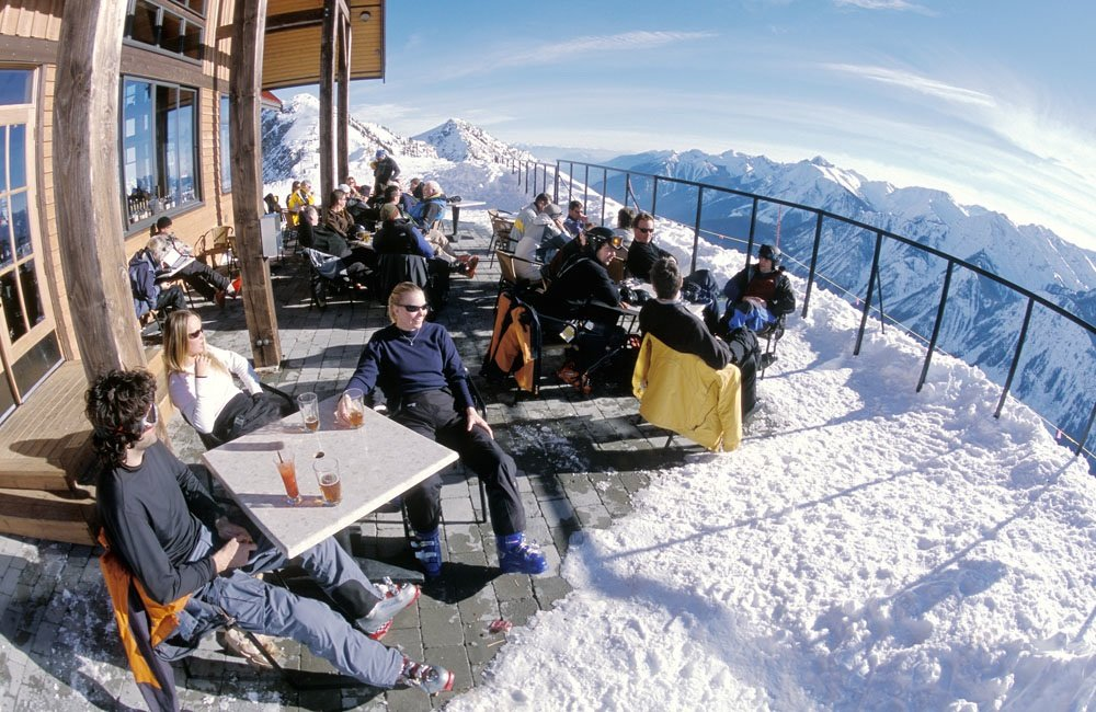 Skiers enjoying apres-ski drinks outside Eagle Eye Deck mountain hut surrounded by snowy scenery