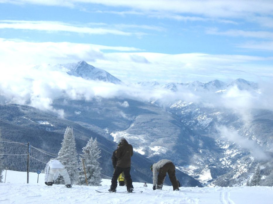Snowboarders look out across the mountains of Vail, Colorado