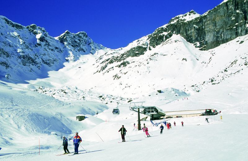 Skiers on the piste with cable cars overhead in Alagna