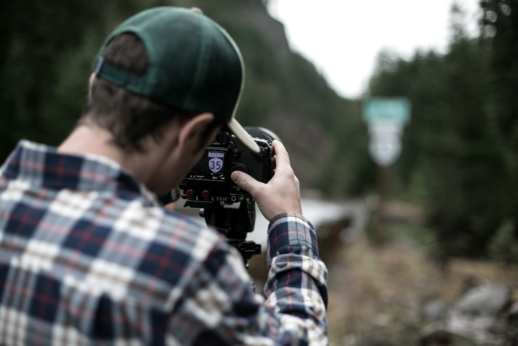 Director of Photography Dane Henry lines up a shot on the road - © Liam Doran
