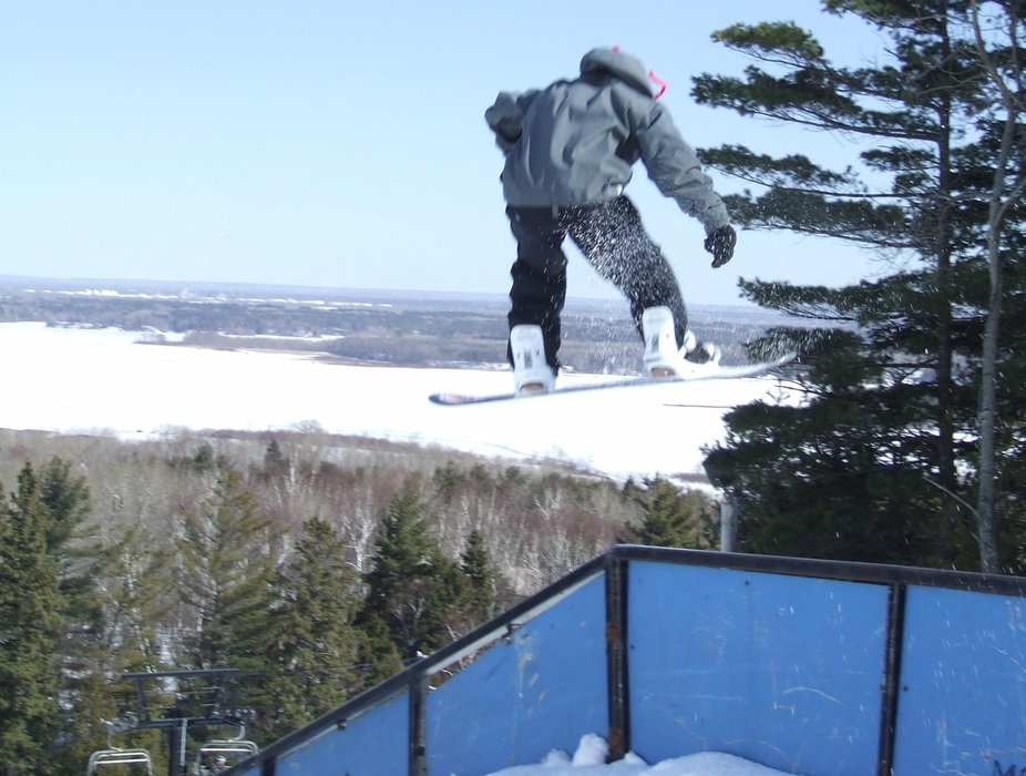 A snowboarder jumps above the rail in the terrain park, Spirit Mountain, Minnesota