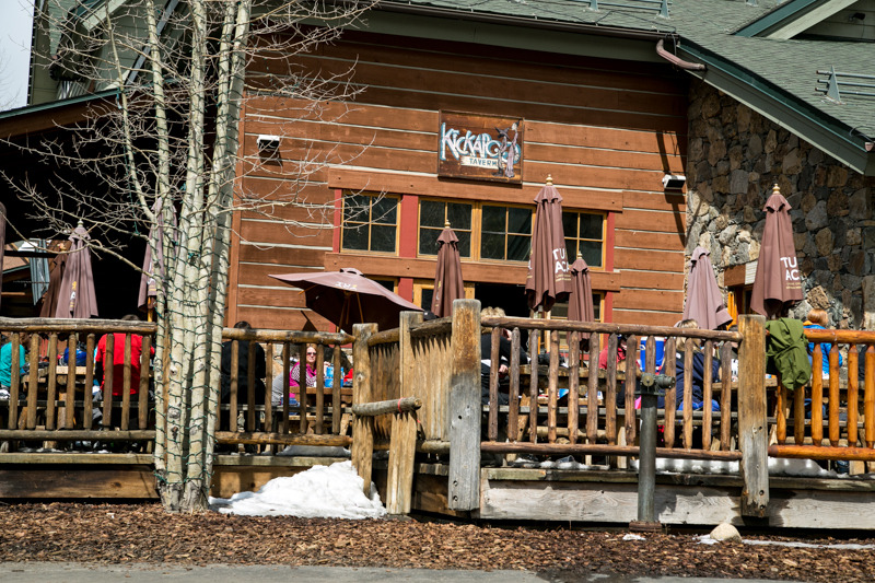 Thirsty skiers and snowboarders take in some sun on the deck at the Kickapoo Tavern in Keystone. - © Liam Doran