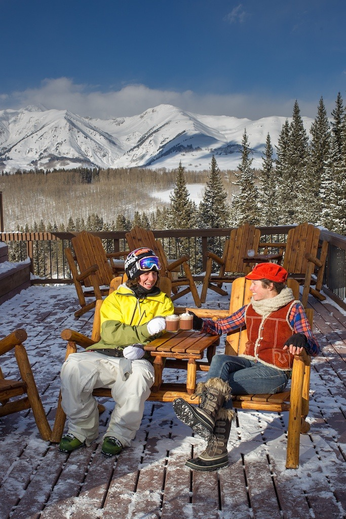 Aidan Sheahan and Crested Butte local, Sarah Joy enjoy a cup of hot coco on a deck on Crested Butte Mountain. - ©Jeff Cricco