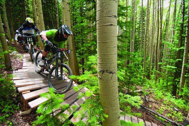 Downhill mountain bikers tackle features in the Evolution Bike Park at Crested Butte Mountain Resort. - ©Trent Bona/Crested Butte Mountain Resort
