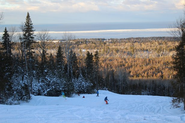 Snowboarders descend Voodoo Mountain with the sun on Lake Superior.  - © Louise Kremer/Voodoo Mountain