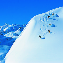 Skiers slaloming over powder at St Anton, AUT. - © St. Anton Tourism
