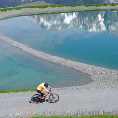 Cyklistika okolo priezračnej hladiny jazera, v ktorej sa zrkadlia štíty hôr - © Puradies Hotel